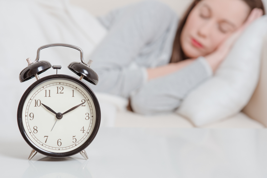 Alarm clock with woman sleeping on the background